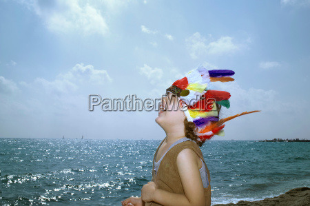 toddler in indian headdress on beach