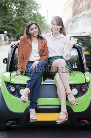 women sitting on car on city