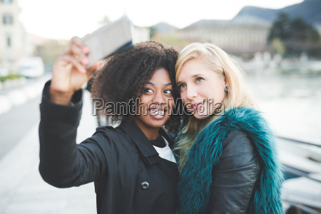 two young women posing for smartphone