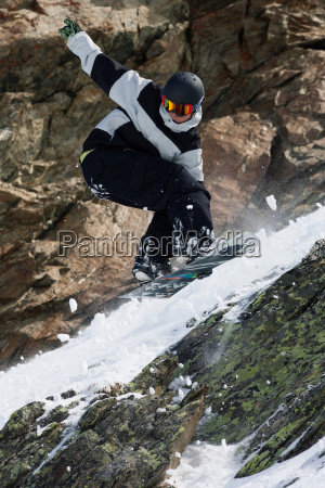 snowboarder jumping on rocky slope