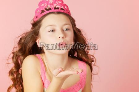 girl in pink tiara blowing kisses