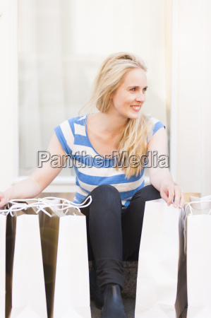 young woman sitting on step surrounded