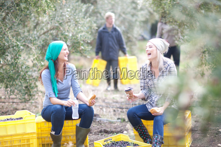 women sitting on crates taking a