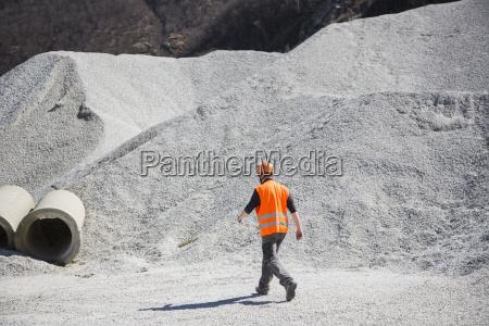 quarry worker walking through gravel mounds