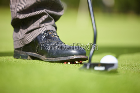 cropped view of golfers foot wearing