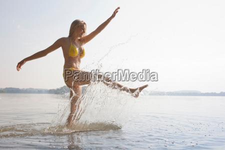 young woman kicking water in lake