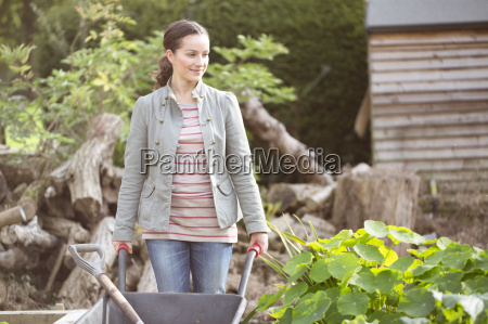 female gardener pushing wheelbarrow in rustic