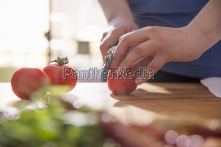 hands of woman slicing tomato at