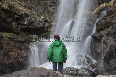 man looking at waterfall river toce
