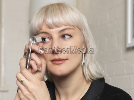 female jeweler examining diamond using magnifier