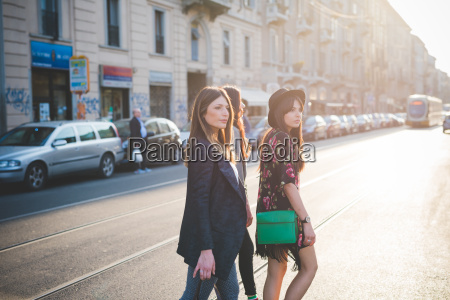 three young women strolling on city