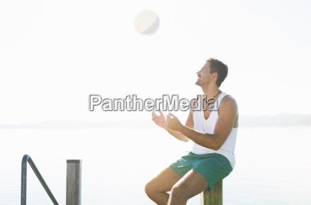 young man throwing beachball at lake