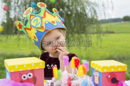 female toddler eating birthday cake in