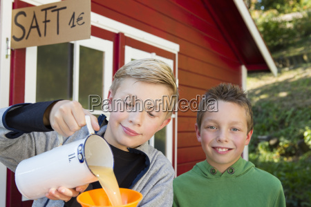 two brothers pouring fresh orange juice