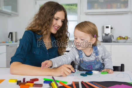 teenage girl and female toddler drawing
