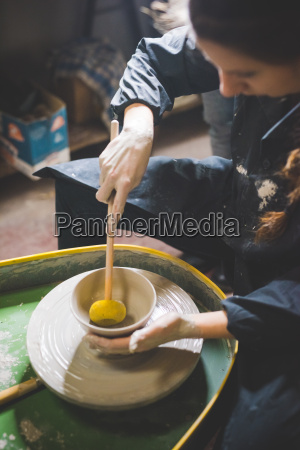 young woman sitting at pottery wheel