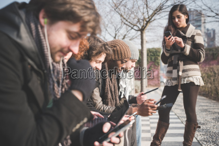 six young adult friends using smartphones