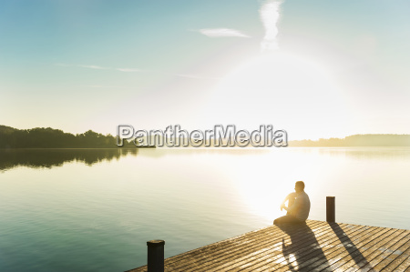 young man sitting on corner of