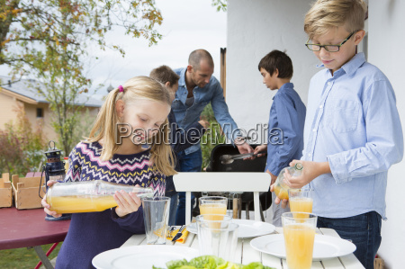girl and brother pouring juice at