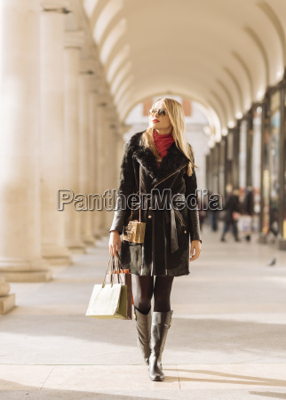stylish young woman carrying shopping bags