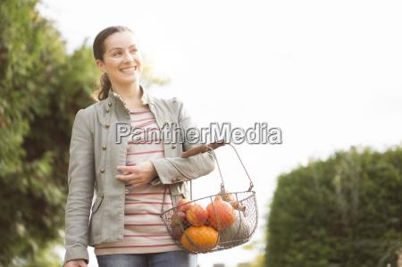 woman carrying basket of organic fruit