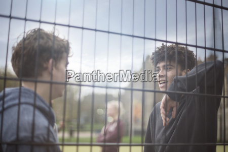 two young men leaning against fence