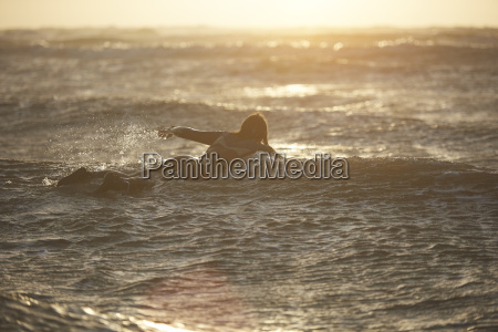 young male surfer paddling out to