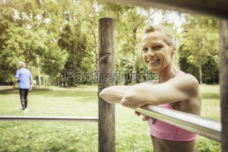 mature woman in park leaning against