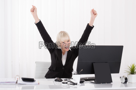 happy businesswoman raising arms at desk