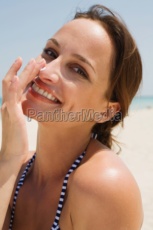 a woman applying suncream