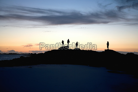 silhouetted people on rocks