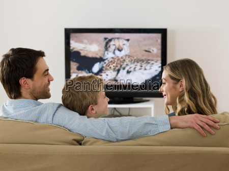 a family watching tv and talking