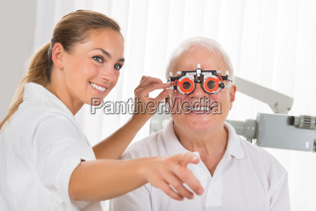 female optometrist checking patients vision with
