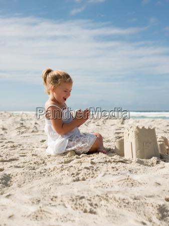 happy girl with sandcastle