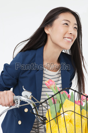 woman riding bicycle with flowers in