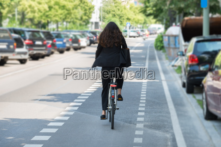 young businesswoman riding bicycle on street