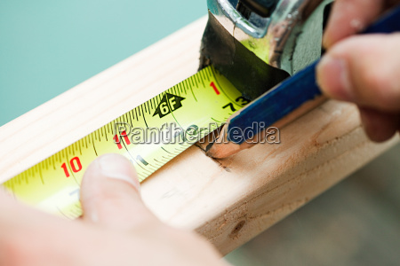 woman measuring plank of wood and
