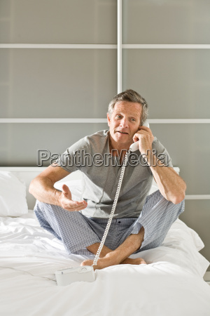 man on bed using telephone