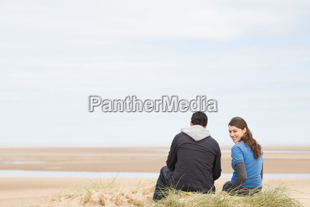 couple sitting on an empty beach