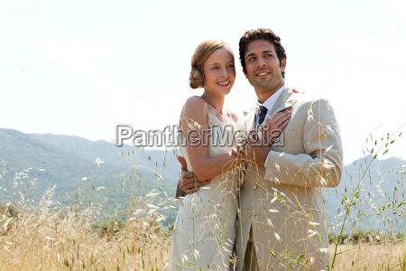 newlyweds embracing in field