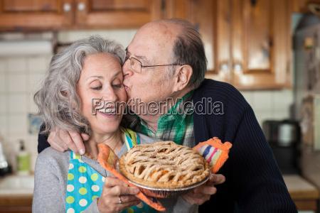 senior man kissing woman holding freshly
