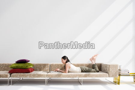 japanese woman relaxing on sofa