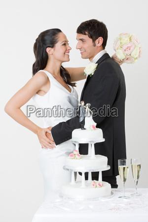 newlyweds standing near wedding cake