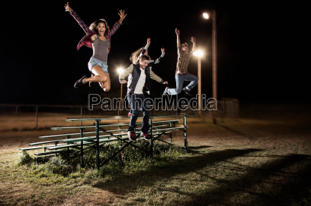 four friends jumping over bleachers at