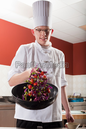 male chef frying with wok in