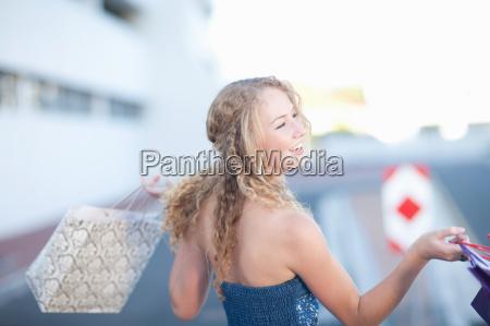 happy young women carrying shopping bags
