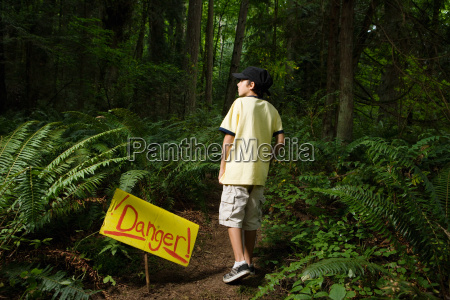boy by danger sign