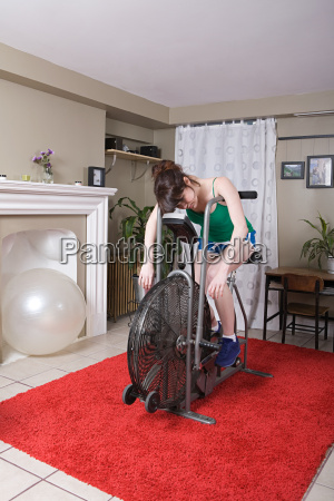 exhausted young woman on exercise bike