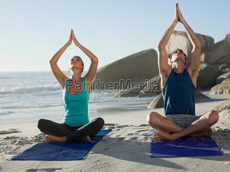 young couple doing yoga on beach