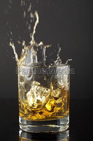 ice cube splashing in tumbler of